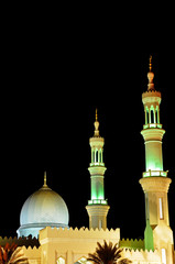 Dome and two minaretes of the Mosque in night in United Arab Emi