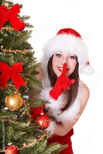 Christmas girl in santa hat making silence gesture.