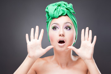 Surprised excited woman with pink-green makeup in green hat