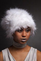 Glamour african woman in white hat and silver necklace
