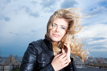 Happy blonde woman with her hair blowing on the roof