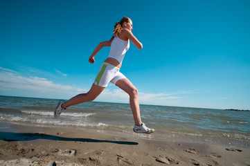 Sport woman running in sea coast