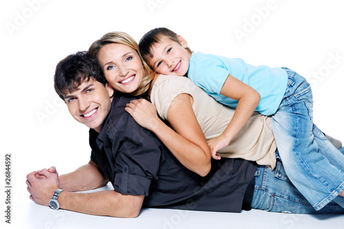 Happy beautiful family with child lying on floor