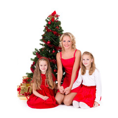 Mother with children sit near Christmas tree.
