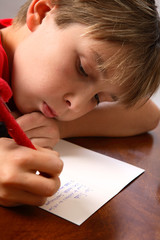 Boy writing note letter to santa