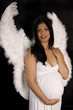 beautiful pregnant woman in white dress and angel wings