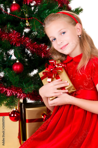 Young girl with gift sit near Christmas tree.