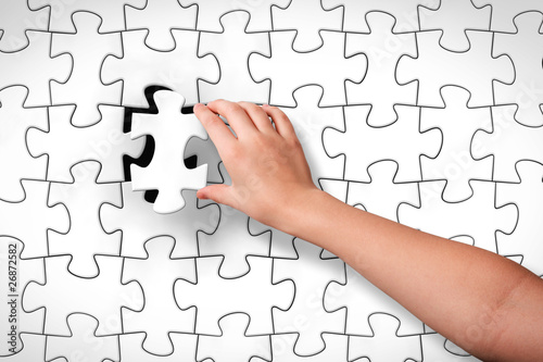 Child's hand, inserting piece of jigsaw puzzle into the hole
