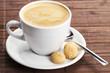 kaffee in einer weissen tasse mit einem löffel und amarettini