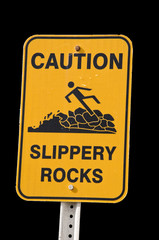 A Yellow Sign Warning of Slippery Rocks Isolated on Black