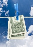 u.s. dollar on rope with clothespin over blue sky