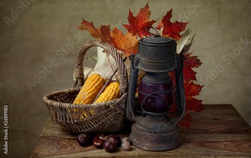 Herbstliches Stilleben mit Petroleumlampe und Mais in Weidenkorb