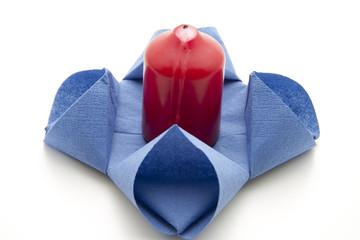 Rote Kerze und blaue Serviette