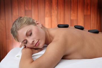 Blond woman laying on massage bed with hot stones