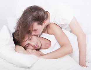 Gay couple kissing on the bed