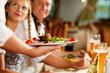 Leinwanddruck Bild - Kellnerin serviert in bayerischem Restaurant