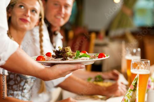 Leinwanddruck Bild Kellnerin serviert in bayerischem Restaurant
