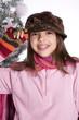 jeune adolescente à la casquette devant le sapin décoré