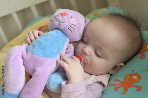 baby sleeping with a cuddly toy