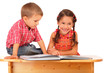 Two smiling children reading the book on the desk