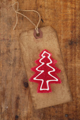 christmas tree red candy on retro paper tag, wooden background