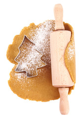 christmas gingerbread tree cookie cutter on dough with rolling p