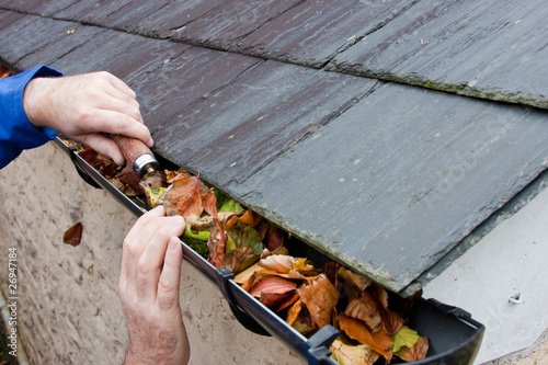 canvas print picture Workman Clearing Autumn Leaves from Gutter