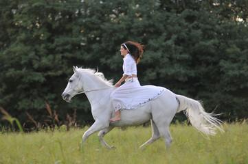 Giovane amazzone su un bianco cavallo