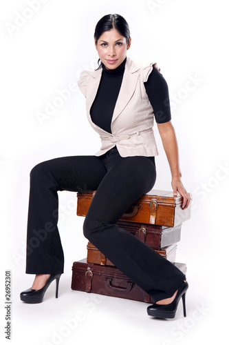 Young brunette sitting on a pile of vintage briefcases.