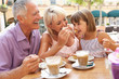 Grandparents With Granddaughter Enjoying Coffee And Cake In Cafe