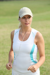 Beautiful blond woman jogging in countryside