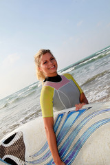 Young woman holding surfboard at the beach
