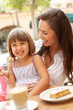 Mother And Daughter Enjoying Cup Of Coffee And Piece Of Cake In