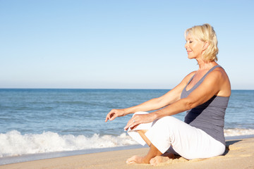 Senior Woman In Fitness Clothing Meditating On Beach