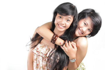 Two girl best friends smiling over white background