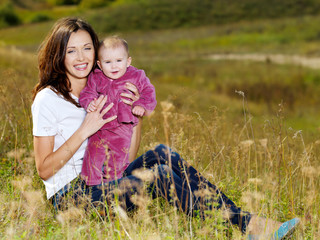 beautiful mather with smiling beby on nature