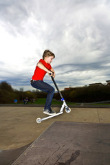 Boy riding a scooter gone airborne on a scooter park