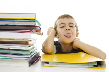Child sticks out his tongue with school books on the table