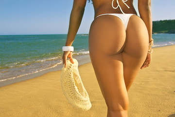 beautiful bikini butt adult model walking beach holding hat