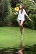 Mujer joven corriendo con flor amarilla