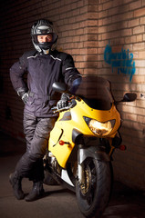 Biker in a black coats and helmet and his motorcycle