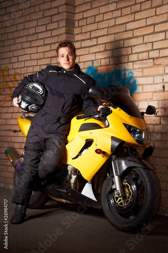 Biker in a black coats and his motorcycle