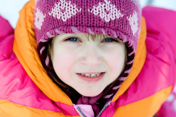 Winter toddler girl in pink hat looking to the camera