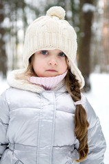 Adorable toddler girl with blue eyes in white warm hat