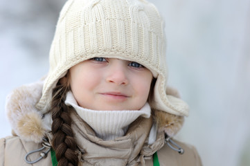 Winter toddler girl in warm hat looking to the camera
