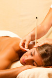 Fototapety Woman with ear candles and gem massage