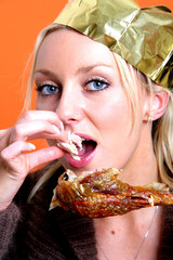 Young Woman Eating Turkey Drumstick. Model Released