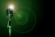 Classic microphone and green light on background