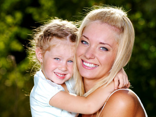 smiling and beautiful mother and little daughter