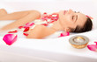 Attractive naked girl enjoys a bath with milk and rose petals